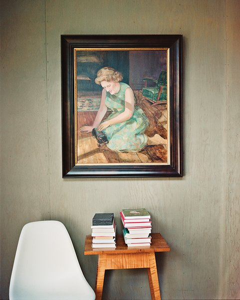One of the bedrooms became a guest room and study, where a portrait of Green's mother by Evelyn Spence-Reeve hangs above a vintage table.