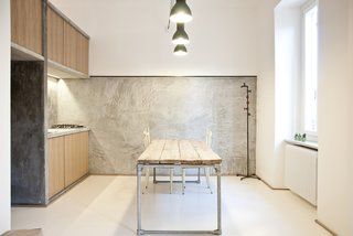 """It was supposed to be as naked as possible,"" says Alexandru Popescu, one of the members of R3Architetti who helped design and build the 3 Vaults apartment. ""The furniture is absolutely included in the architecture; it's more like an indoor landscape instead of a typical open plan."" The kitchen exemplifies their approach, with textured concrete walls contrasting with wood panels and salvaged industrial lighting. The table, custom built by R3Architetti, is made in part from pipes procured from one of their fathers, a plumber."