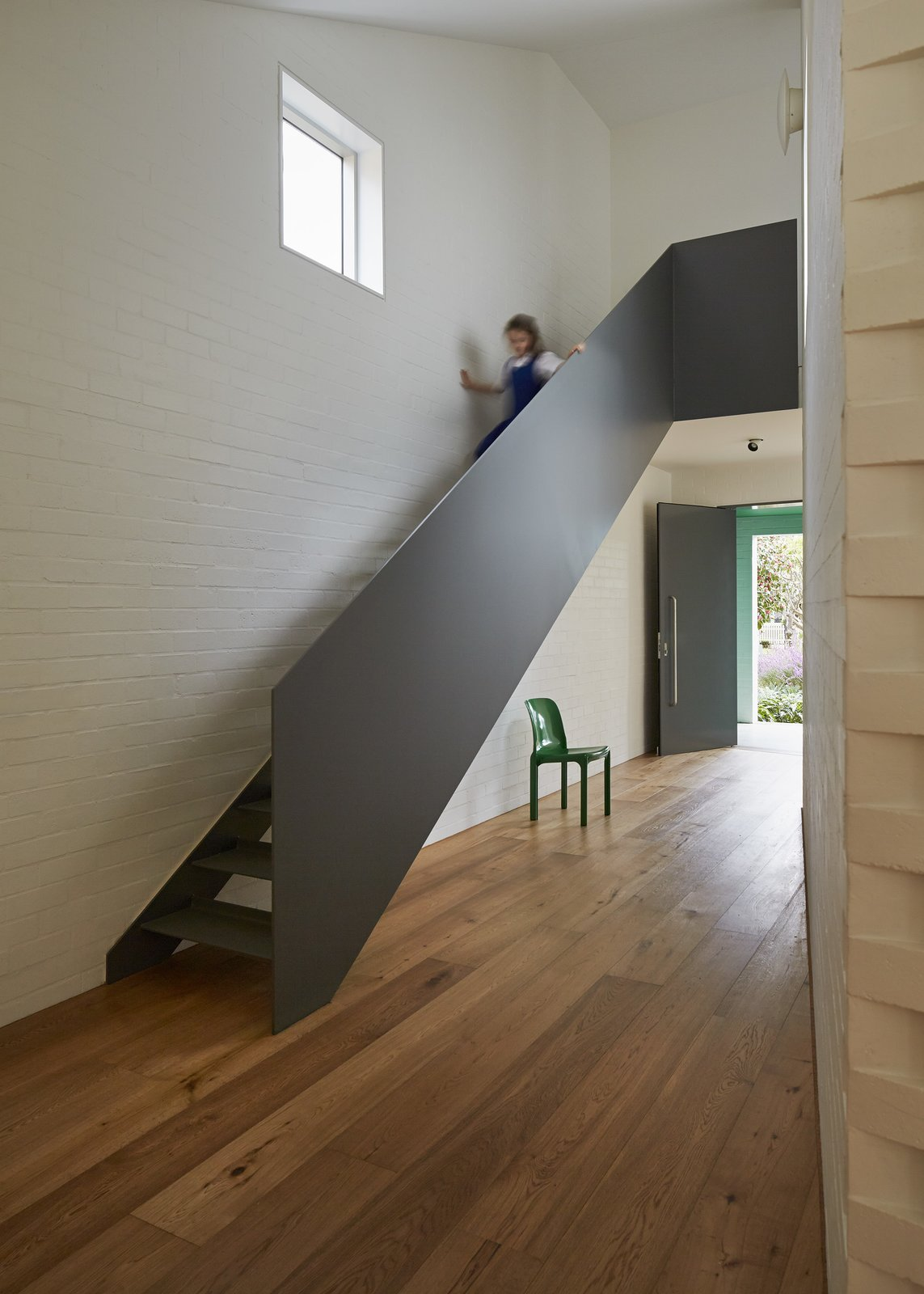 At the top of the steel staircase, a window-lined hallway wraps around the inner courtyard as it leads to the playroom. The upper level also includes the children's bedrooms and bathroom.  190+ Best Modern Staircase Ideas from Riverview