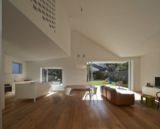 """""""The walls are painted brick to reinforce the connection to the exterior of the house,"""" Trimble says of the combined dining and living area. Clad in European oak flooring, the warm space features Series 7 chairs by Fritz Hansen, a Soverin Table by Andreu World, and a comfy, leather Marenco sofa by Arflex."""