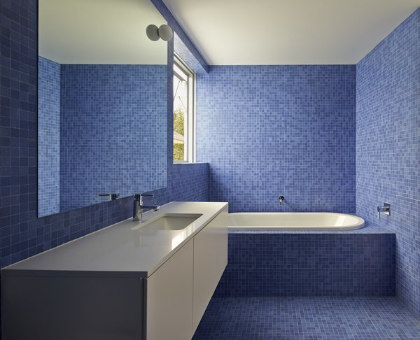 This bathroom, tiled in bright blue mosaic to offset the home's limited materials and color palette, calls for a simple vanity. The sinks, toilets, and tubs are by Villeroy & Boch, while the faucets and towel rails are by Grohe and Avenir, respectively.