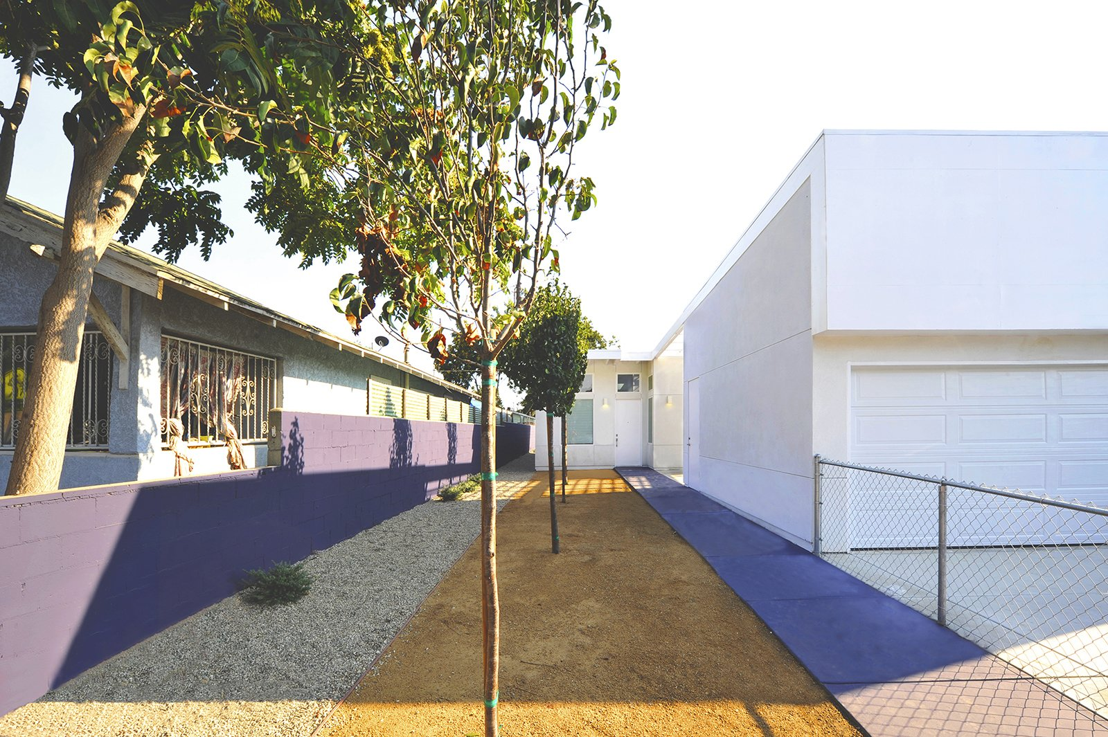 """The houses, like the 53rd Street Prototype, feature lean and gracious walkways to the front door. """"Though these prototypes are set in economically challenged neighborhoods of South Los Angeles, their design provides for integrated defensible space while maintaining openness and connection to the outdoors,"""" states the project description.  Photo 4 of 11 in Vibrant Affordable Housing Prototypes in Los Angeles"""