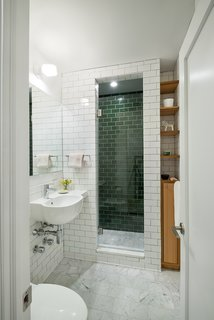 An updated bathroom features a mix of tiles: Carrara marble tiles on the floor, green subway tiles from Heath Ceramics on the inner shower walls, and white subway tiles from Daltile on the exterior walls. The fixtures are from Grohe.