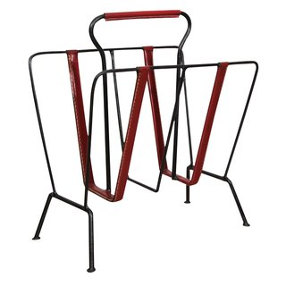 French designer Jacques Adnet (1904–1984) was particularly well known for his deft incorporation of leather elements into his furniture pieces. This rack, created sometime in the 1950s, is constructed of patinated wrought iron and delicately stitched red leather straps. For more information, contact Pascal Boyer Gallery.