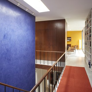 The interiors of Hugh Smallen's 1963 Becker House are accented by a rich blue that connects the two levels, while a vibrant yellow draws attention towards the living room.