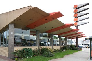 Norms debuted in 1949 at the famed corner of Sunset and Vine in Hollywood. The 24-hour coffee shop chain, founded by Los Angeles-native Norm Roybark, opened its La Cienega flagship location in 1957. Architects Louis Armet and Eldon Davis, who were known for their post-war Googie architecture, designed the building with a large, neon, saw tooth pennant sign to attract the attention of passersby and to echo the futuristic diamond-shaped roofline and geometric elements throughout the diner.
