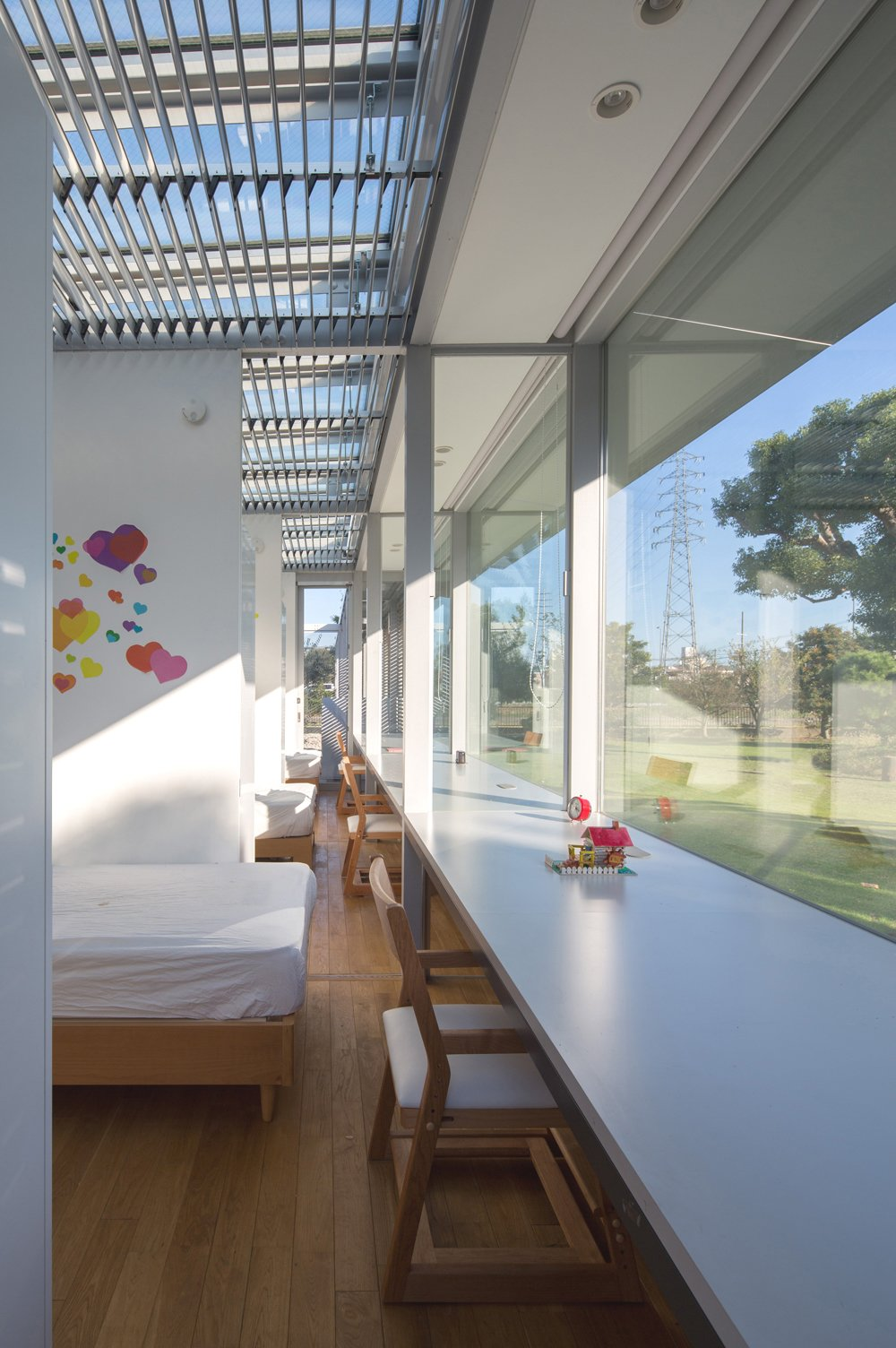 Kids Room and Bedroom Room Type The girls' bedrooms are partitioned by sliding screen panels, which can be opened for access or shut for for privacy. Each room enjoys a stunning wall-to-wall exterior view.  Bedrooms by Dwell from A Green House in Japan Sets the Stage for Family Time