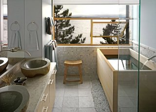 "Grace Boyd's favorite room has a stunning view of Puget Sound reflected in the Hinoki tub she had custom-sized by Roberts Hot Tubs. The clean lines of soaking tubs ""work well in conventional bathrooms,"" says Roberts' Andrew Harris, ""no need to make the whole room Japanese-style."" Grace echoed the grey of the sea and sky in the sinks and the silvery pebbles around the tub. After 32 years in West Seattle, she asked architect Mark Travers to build her a new house in the same spot- she couldn't bear to lose her view. Tubs are popping up in real estate listings as a selling point; new owners can have an existing tub sanded to reveal a fresh layer of pristine scented wood. Photo courtesy of: Roberts Hot Tubs"