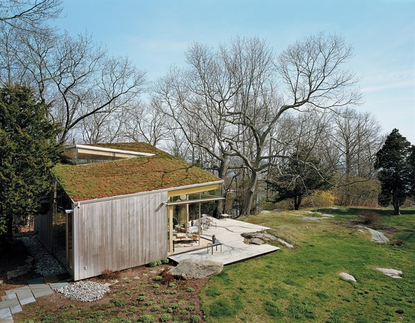 The deck, fashioned from ipe, was built around one of the property's many granite outcroppings. An earthen roof was planted with the same varieties of sedum that were added to the front of the cottage. Photo by: Mark Mahaney