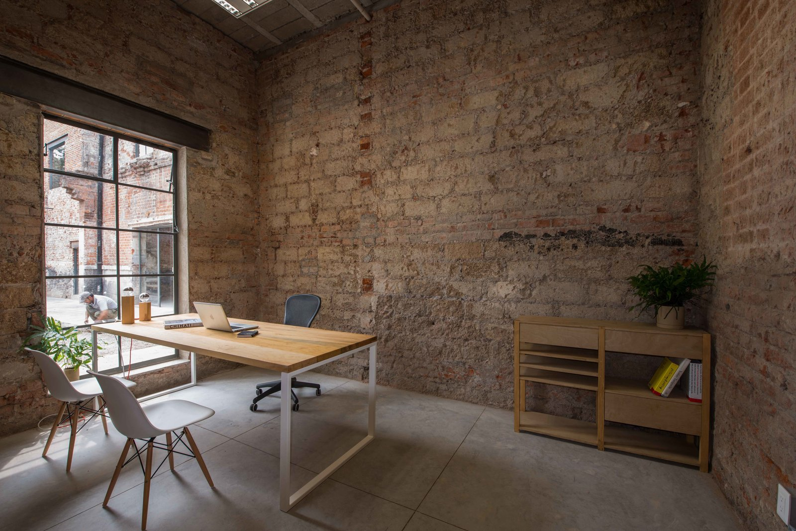 The firm added some windows to direct attention to the interior garden area. Eames shell chairs and an Aeron chair from Herman Miller surround a custom desk.  exposed brick from Modern Office Space Carved Out of a Crumbling Brick Building