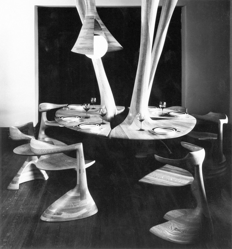 Douglas Baker, a Rochester-based graphic designer, commissioned Castle to create one of his furniture-as-architecture installations for Baker's dining room. What Castle did was nothing short of miraculous: an acrobatic feat of woodworking that flipped the laminated white-oak dining table on its head and suspended it from the ceiling, complete with conical lighting fixture. Sadly, the set-up no longer exists as it did in 1966 (pictured here).  Wendell Castle's Volumes by Kelsey Keith