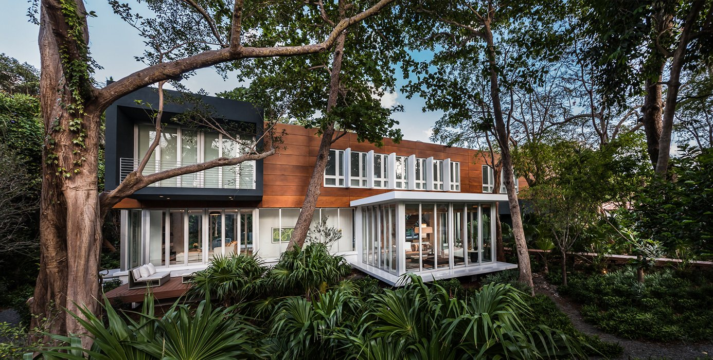 Exterior, Stucco Siding Material, Wood Siding Material, and House Building Type The house is located in the Camp Biscayne area of Coconut Grove, a neighborhood in Miami. Its main volume is clad in Prodema.  Photo 1 of 12 in This Modern Miami House Feels Like It's in the Middle of the Jungle