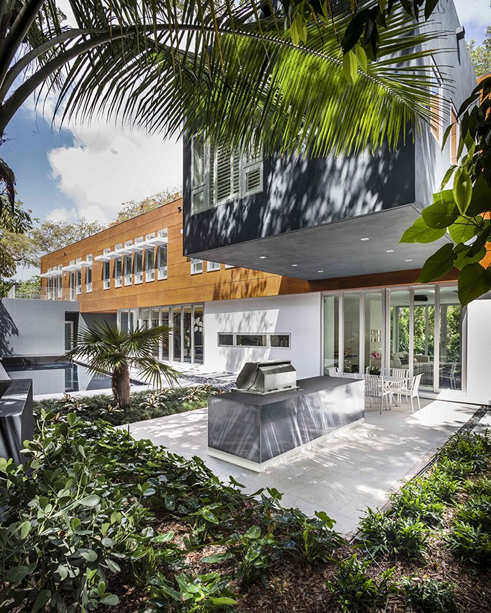"""Outdoor, Trees, Shrubs, Concrete Patio, Porch, Deck, and Back Yard Architect Allan Shulman tackled one of Miami's biggest architectural challenges when he designed a two-story home on a leafy lot dominated by a """"solution hole,"""" a depression in the limestone terrain caused by erosion. Inspired by the jungle scenery of painter Henri Rousseau, Shulman strove to leave the delicate habitat undisturbed. An elegant pool and outdoor kitchen extend from the living areas.  Photo 5 of 12 in This Modern Miami House Feels Like It's in the Middle of the Jungle"""