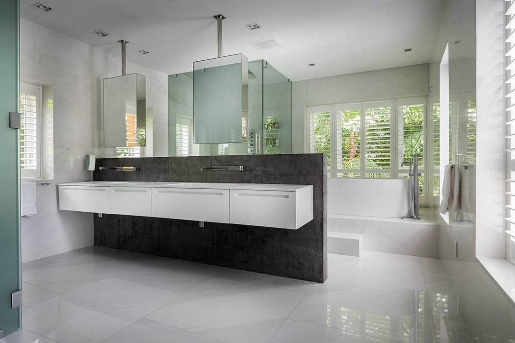 Echoing the facade, dark stone and wood are used throughout the interiors.  Photo 9 of 12 in This Modern Miami House Feels Like It's in the Middle of the Jungle