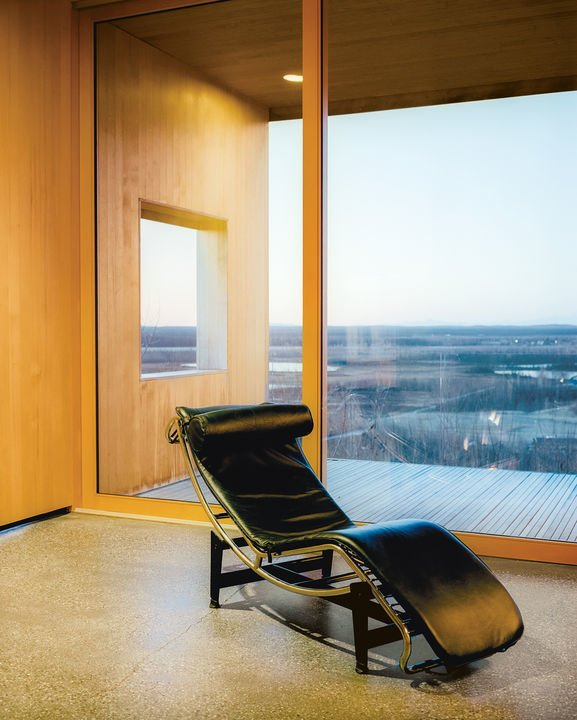 The curvilinear form of the LC4, shown here in black leather, contrasts nicely with the large rectangular windowpanes of this Alaskan cedar cabin.  Photo 6 of 10 in The Woman Behind Le Corbusier's Iconic Chaise Almost Didn't Get the Job