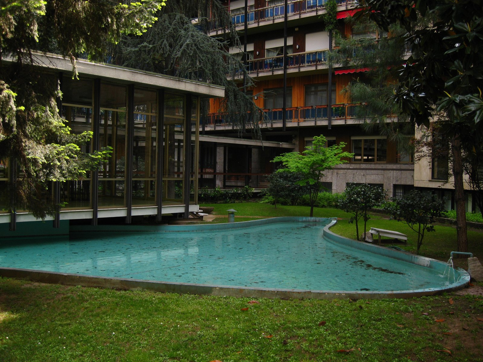 More of a reflecting pool than a swimming pool, the organic shape of this kidney-shaped pool contrasts with the otherwise rectilinear forms at this Modernist apartment building in Milan.  Photo 8 of 11 in The Rise of the Kidney-Shaped Pool—and its Unexpected Impact on Skate Culture from Spazzio Rossana Orlandi