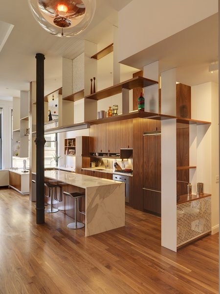 BSC designed suspended powder-coated and walnut open shelves to demarcate the kitchen from the rest of the living space. The detailing on the cast-iron columns inspired the perforated pattern of the semi-transparent screens.  Photo 4 of 7 in Luminous Apartment in a Historic NYC Building
