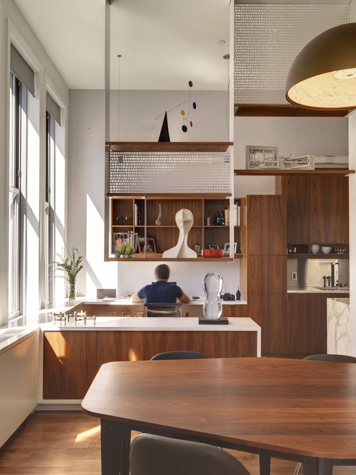"""The open shelving reaches to the apartment's 13-foot ceilings, bringing the eye's attention upwards. Built-in furniture, like the desk Bart works at, was designed throughout the apartment. The couple imagine the desk will be taken over by their children once they're old enough to do homework. """"The design of the space allows us to spend time together, even when we're doing different things,"""" Bart says, of the open floor plan.  Photo 5 of 7 in Luminous Apartment in a Historic NYC Building"""