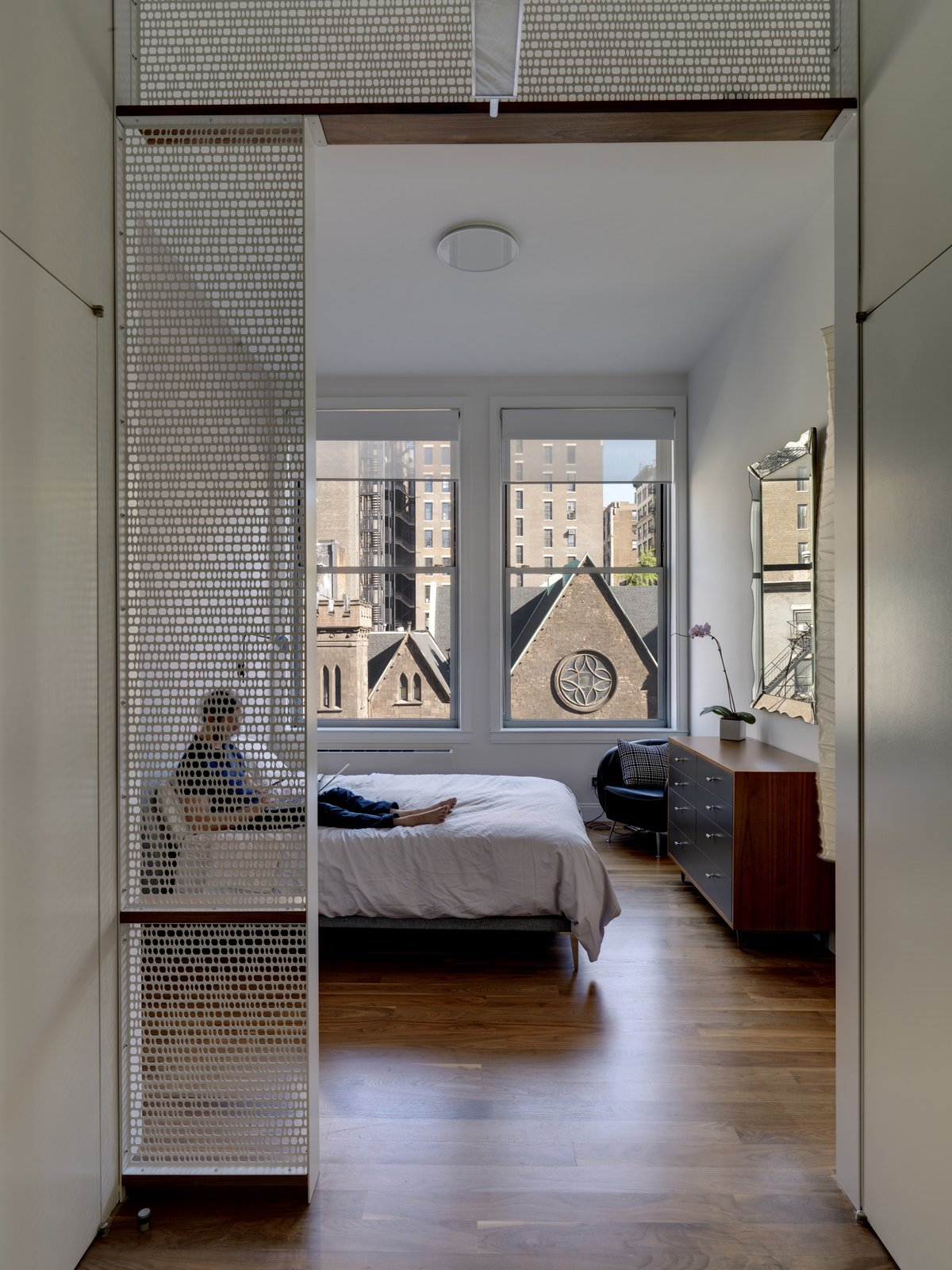 The screens and shelving from the kitchen area repeat in the master bedroom, filtering light to the closet area, through which the master bedroom is accessed. The dresser was designed by BSC.  Bedrooms by Dwell from Luminous Apartment in a Historic NYC Building