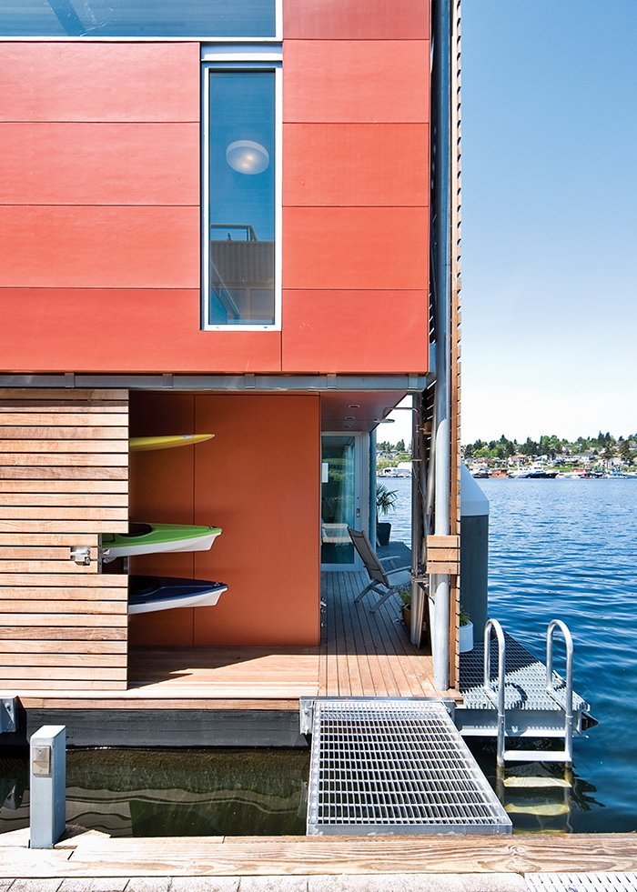 The exterior of a floating house in Seattle is clad with fiber cement panels from James Hardie painted in three slightly different hues: Fiery Opal, Navajo Red, and Rich Chestnut by Benjamin Moore.  Photo 2 of 3 in This Couple Merrily Floats Along in Seattle from How to Build a Floating Home