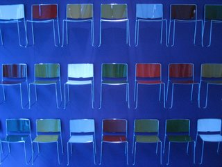 The Porro showroom was bathed in a deep blue light, with an impressive installation of multicolored Spindle chairs lining the wall.