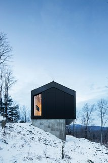 The project's unique challenges—a tight budget and steep, difficult terrain—led architecture firm _naturehumaine to a creative solution that gave the house its delightfully sculptural appearance. Making the first floor's envelope slightly narrower than the top one's saved money while minimizing the amount of excavation required.