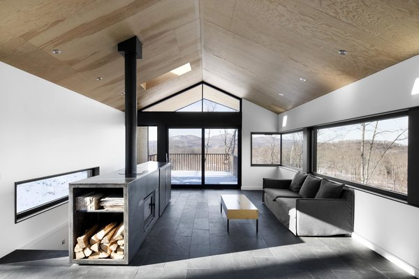Architecture firm _naturehumaine designed a dream hideaway in eastern Quebec, complete with a centralized fireplace. The modern fireplace was built into a custom, multi-purpose cabinet welded from sheets of hot-rolled steel. It stores firewood on one end with an open shelve, holds a TV, and even acts as a guardrail for the staircase.
