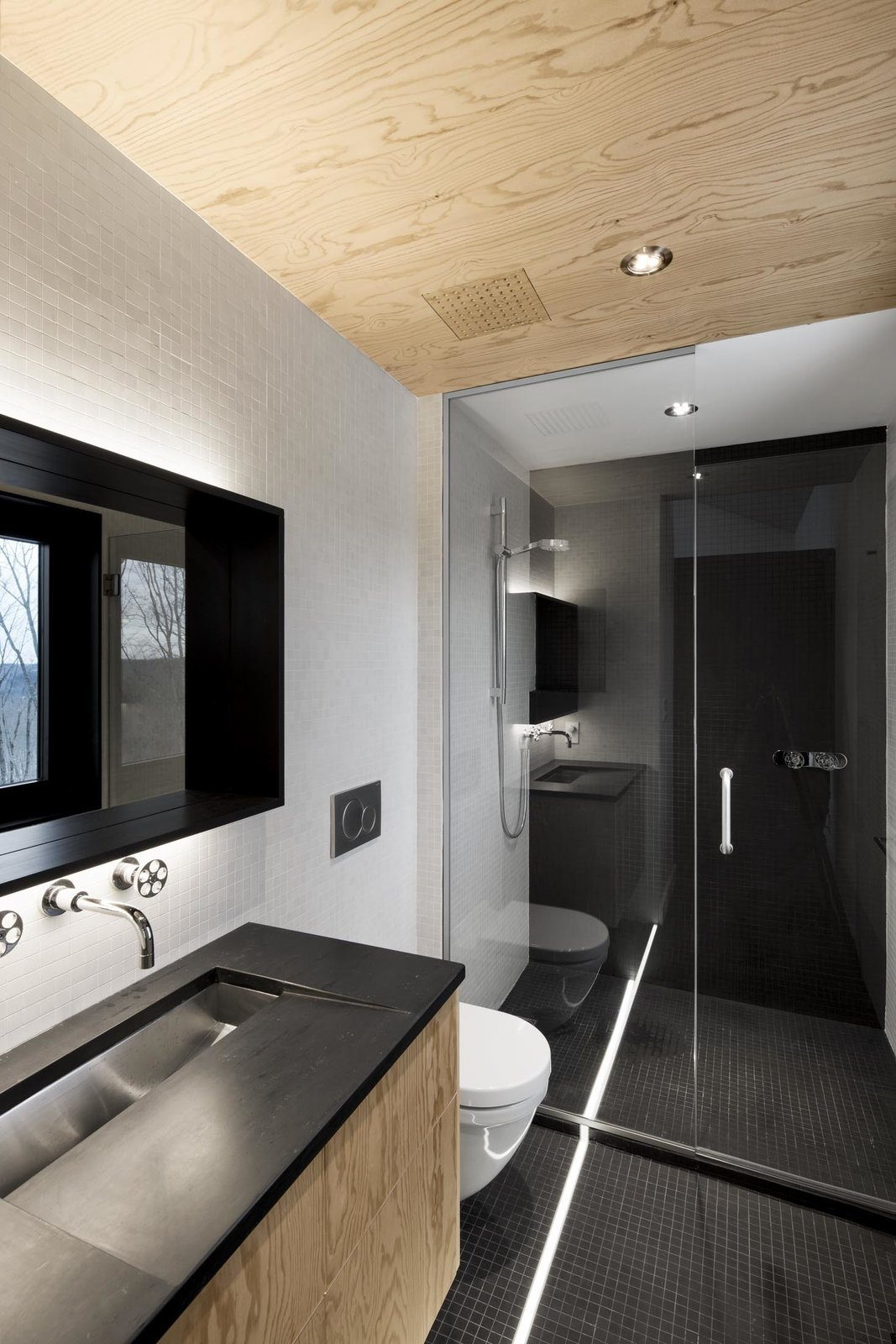 In the bathroom, the architects mounted a Kohler sink on a sloped, custom-slate countertop. Since the stone doesn't hold up well in water, the architect switched to black mosaic tile in the shower. The faucets are from Cabano's Century series. Tagged: Bath Room, Ceramic Tile Floor, Undermount Sink, Full Shower, Ceiling Lighting, and Enclosed Shower.  Bathroom from Amazing Cantilevered Home in the Mountains