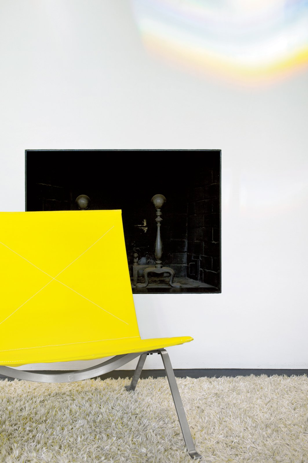 Living Room, Chair, and Rug Floor A PK 22 Easy Chair by Poul Kjaerholm for Fritz Hansen adds a dash of yellow to the breakfast room.  Photo 7 of 8 in A Traditional Home and an Impeccable Eye