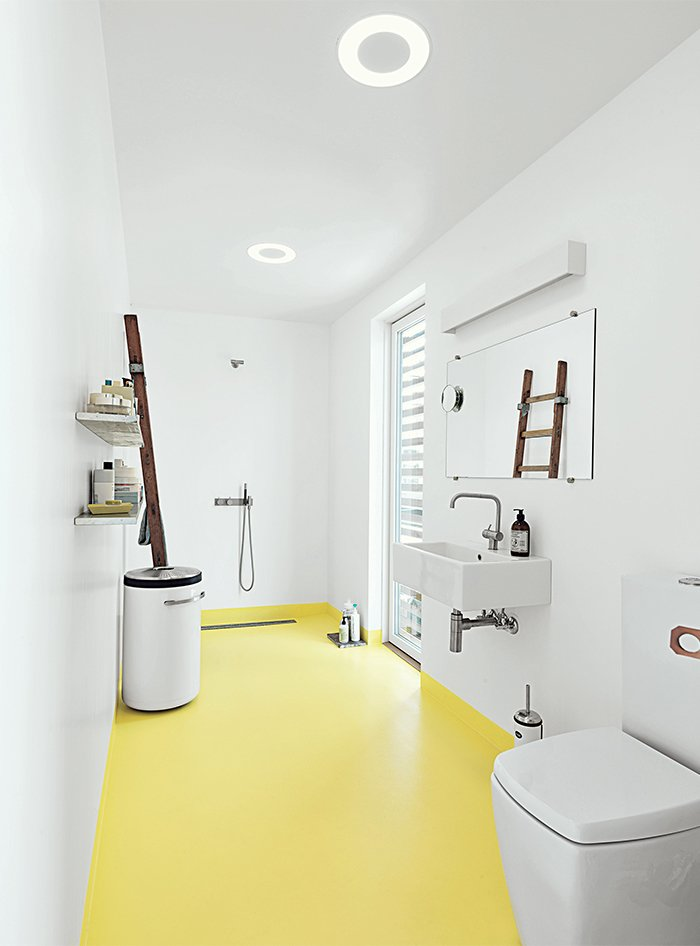 Bath Room, Linoleum Floor, Wall Mount Sink, Open Shower, Recessed Lighting, and Two Piece Toilet In the bathroom, the home's epoxy floor transitions from whitish gray to submarine yellow. The sink and tub are by Galassia, and the faucets are by Vola. A ladder, which serves as a towel rack, was sourced from the Danish Emergency Management Agency. The black-and-white industrial laundry bin is by Vipp.  Surprisingly Colorful Bathrooms by Luke Hopping from Each Day at This Floating Home Begins With a Swim, Just Two Feet From Bed