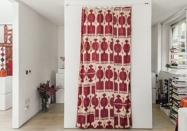 A handwoven silk ikat print, which Molineus acquired in Uzbekistan, is draped between the kitchen entrances. A Sapiens bookshelf by Bruno Rainaldi stands at far right.