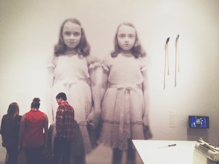 The infamous Grady Twins from The Shining (1980) look unfazed, as a small group of visitors focus on an exhibition reading.