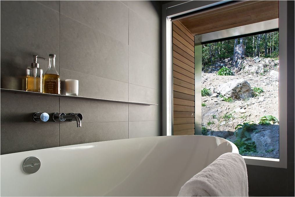 Bath Room and Freestanding Tub The bathroom was similarly designed to make the most of exterior views.  Best Photos from Modern Interiors in British Columbia