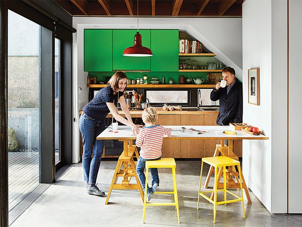 Artist Stephen Waddell and wife Isabel Kunigk—a landscape designer—remodeled their 1,300-square-foot bungalow with a raised roof and a kitchen that opens up to the living room. The apple-green cabinets were made by Waddell and a friend, and yellow stools add a playful touch.