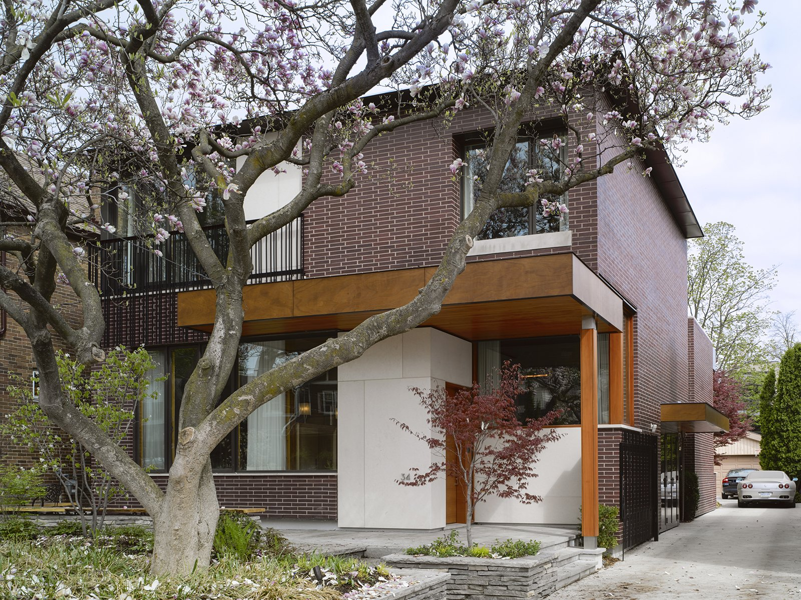"""The house responds to its site. """"The design was directly influenced by two mature, century-old magnolia trees in the front and a Japanese maple in the rear,"""" Tedesco says. """"The location of widows and main program spaces, such as the living room and master bedroom, were strategically placed to take full advantage of views of these trees. Because the trees are fully visible from the interior, seasons and the trees' yearly blooming cycles play a significant role in daily life—they're not just landscape elements. The window sizes and their locations were coordinated with the existing trees to take advantage of passive solar shading in the summer and solar gain in the winter months when the trees do not have foliage.""""  Photo 2 of 11 in Smart Tech Makes this Modern Home Ultra Energy Efficient"""