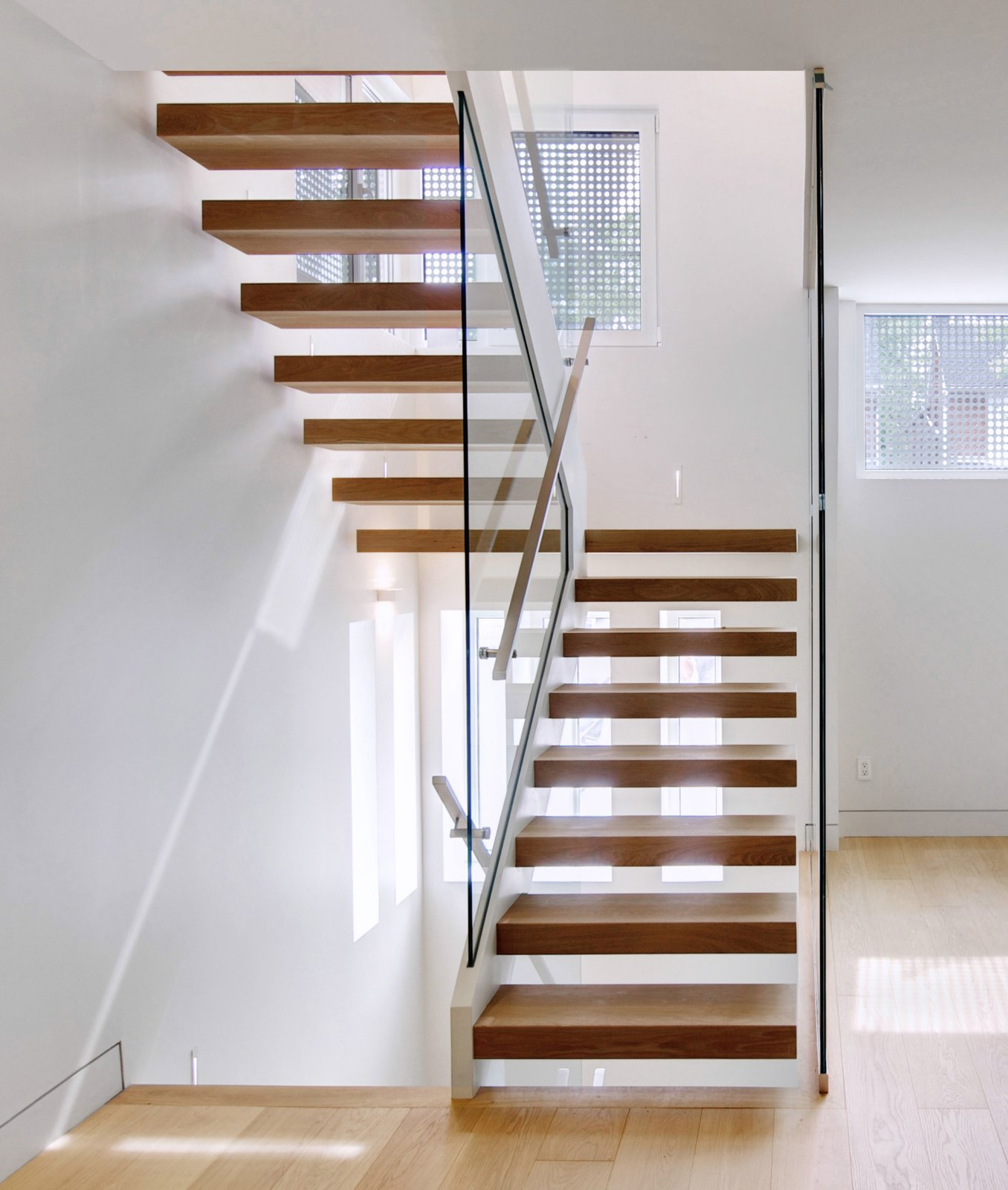 Another peek at the perforated interior windows, which are made from cropped sections of the steel wall in the courtyard.  190+ Best Modern Staircase Ideas from From a Flower Bulb Factory to an Entertainment Hub
