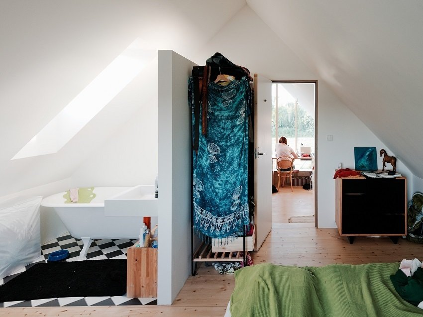 Bedroom, Wardrobe, Dresser, Bed, and Light Hardwood Floor The back bedroom and small bathroom benefit from warmer, more playful flooring, including the geometric black-and-white pattern below the tub.  Photo 8 of 8 in Small Country Home with Dramatic See-Through Wall