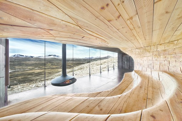 The Norwegian Wild Reindeer Pavilion by SNØHETTA offers visitors a perch to watch wild reindeer herds in the mountains of central Norway. It features a smooth wood ampitheater and a wood-burning stove.