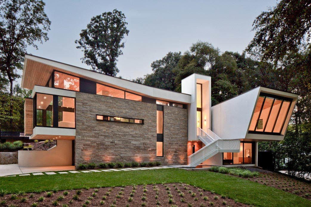 """Svenson calls the floating aluminum stairway """"a major sculptural element."""" He adds, """"We really wanted to celebrate the entry,"""" which is elevated because the site is ten feet higher in the rear. The earthy stucco and local stone cladding keep the home rooted to its landscape.  Photo 2 of 7 in A Wing-Roofed Home in Georgia Perches Among the Trees"""