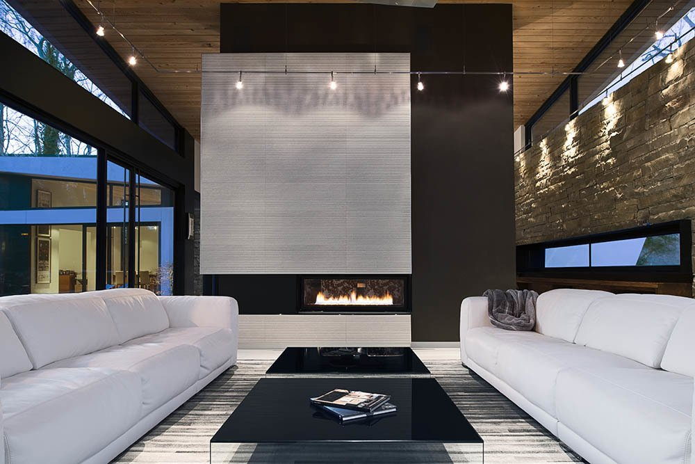 The clients asked for interior products in thirteen shades of white, including the twin Malibu sofas by American Leather. Interior designer Burns Century added deeply hued textures such as the charcoal suede on the fireplace column to keep the room feeling natural, not icy. The black Pool coffee tables are from Design Within Reach.  Photo 4 of 7 in A Wing-Roofed Home in Georgia Perches Among the Trees