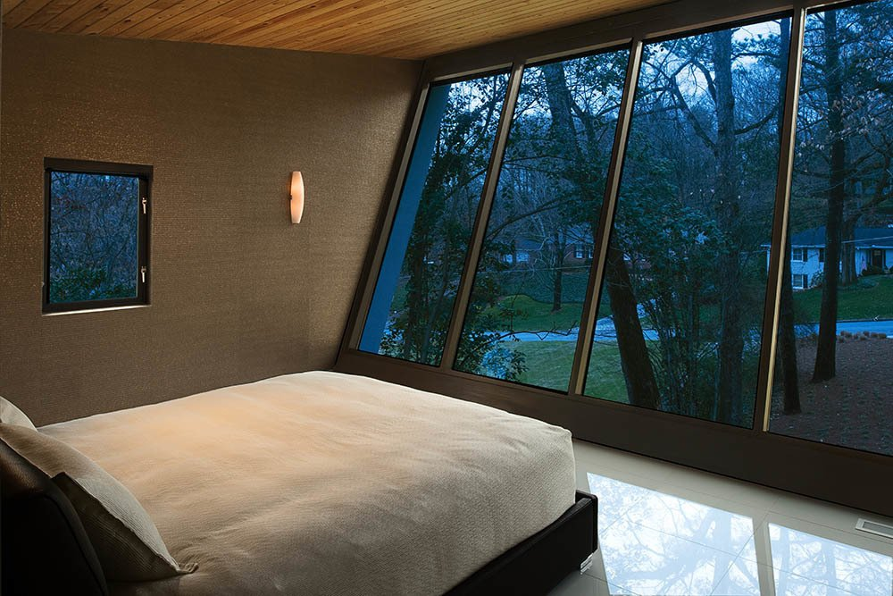 Lustrous textures characterize the cantilevered master bedroom. The gleaming four-square-foot white porcelain tiles are softened by crushed-shell wallpaper and a cypress ceiling. Tagged: Bedroom and Bed.  Photo 6 of 7 in A Wing-Roofed Home in Georgia Perches Among the Trees