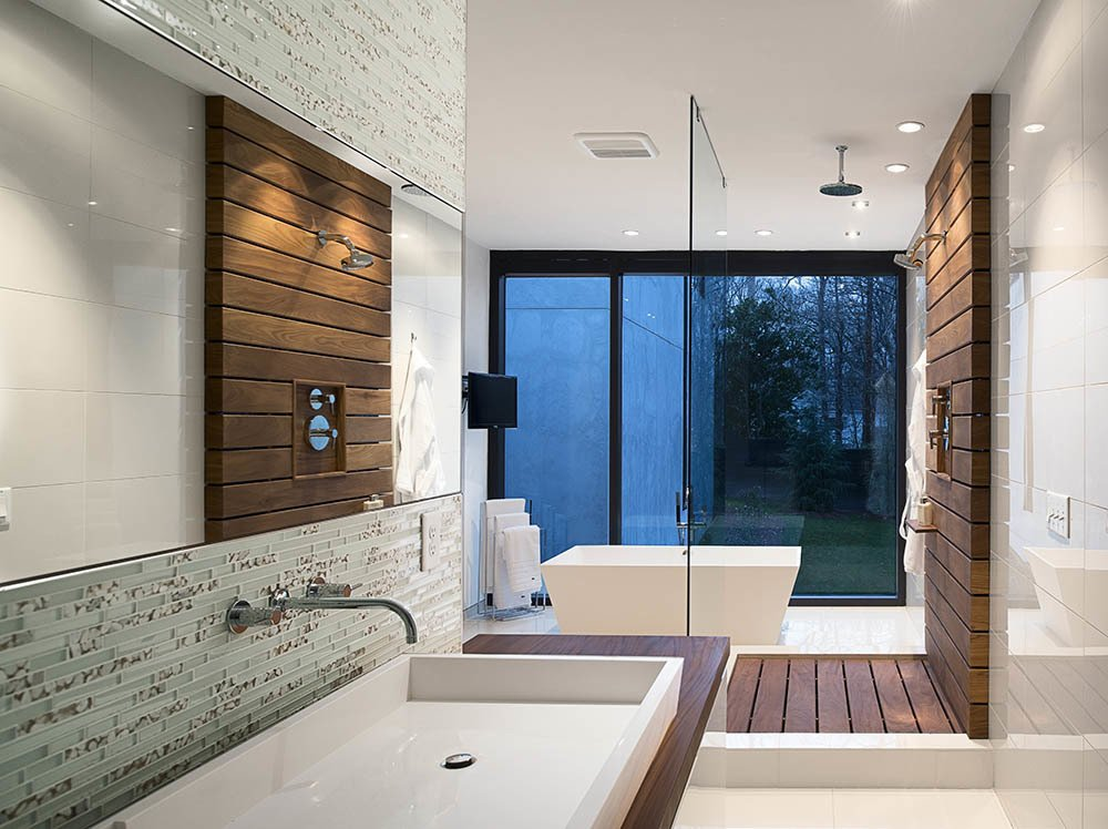 Bath Room, Wood Counter, Vessel Sink, Glass Tile Wall, Freestanding Tub, and Open Shower In the master bath, a custom raised Silestone sink is surrounded by a teak countertop and Porcelanosa glass tiles. Teak slats anchor the glass-enclosed shower.  Photo 7 of 7 in A Wing-Roofed Home in Georgia Perches Among the Trees
