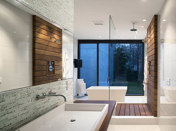 In the master bath, a custom raised Silestone sink is surrounded by a teak countertop and Porcelanosa glass tiles. Teak slats anchor the glass-enclosed shower.