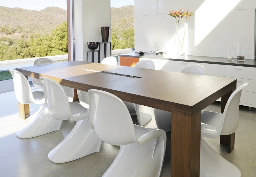 The Plyned dining table from Viesso is a graceful, yet structured modern design. Made completely from solid bamboo, the edges offer a layered surface. The trough option adds an interesting visual element and functional space. Also available in custom dimensions to fit your space and four different bamboo colors. Vitra's white Panton chairs line the perimeter of the table to give this dining room a midcentury look.  Modern Dining Rooms by Allie Weiss