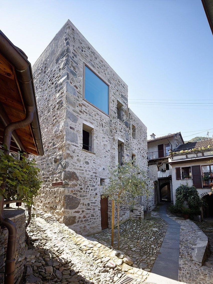 """The end goal, a vacation home with a view of the nearby lake, led Jérôme de Meuron to cut through a wall and ceiling to open up the space. """"We tried to preserves as much as possible,"""" he says. The addition of the large upper story window adds daylight without altering the street-level character of the stone home.  Scaiano Stone House by Patrick Sisson"""