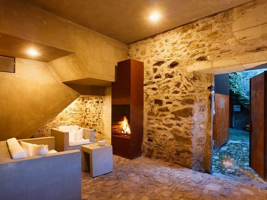 The former cellar, now an entrance with a built-in raw steel fireplace, welcomes guests. Plaster outlines the new staircase, where an old stonewall was cut out to provide a passageway to the upper level.  Scaiano Stone House by Patrick Sisson