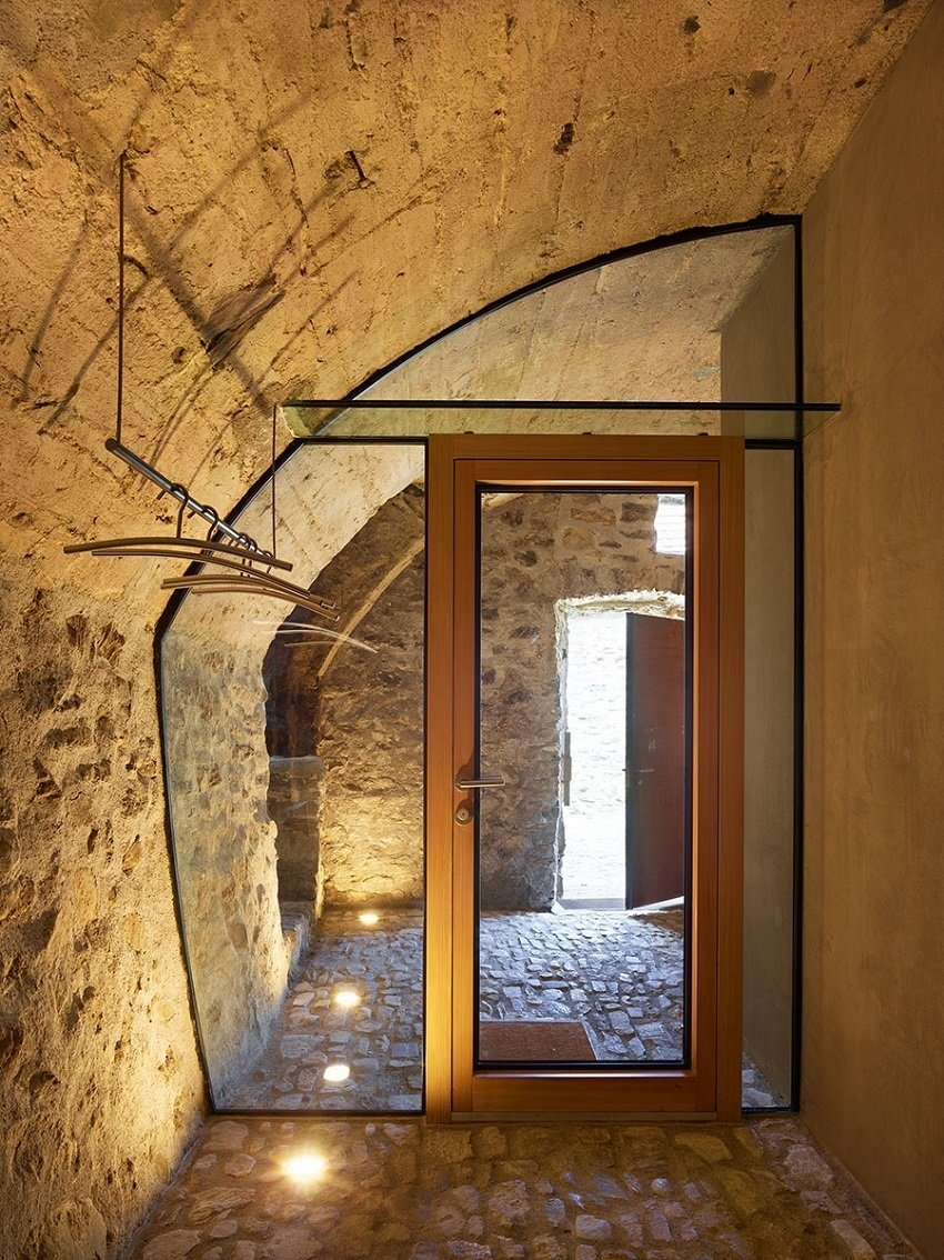 "Dramatic floor lighting on this glass wall, custom fit within the curve of a carved-out stone wall, provides simple beauty in material contrast. ""In such small spaces, it's often better to integrate the furniture and fixtures into the room,"" says de Meuron.  Scaiano Stone House by Patrick Sisson"