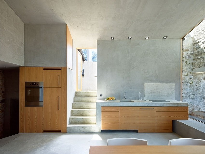 This alternative view of the kitchen and dining area, outfitted with KWC ONO and Sanitär Tröesch, exemplifies how reinforncing the walls and cutting through some of the stone brought significant light into the interior.  Scaiano Stone House by Patrick Sisson