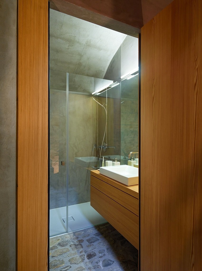 Custom case work and a polished wall give the bathroom a warm yet minimal look.  Scaiano Stone House by Patrick Sisson
