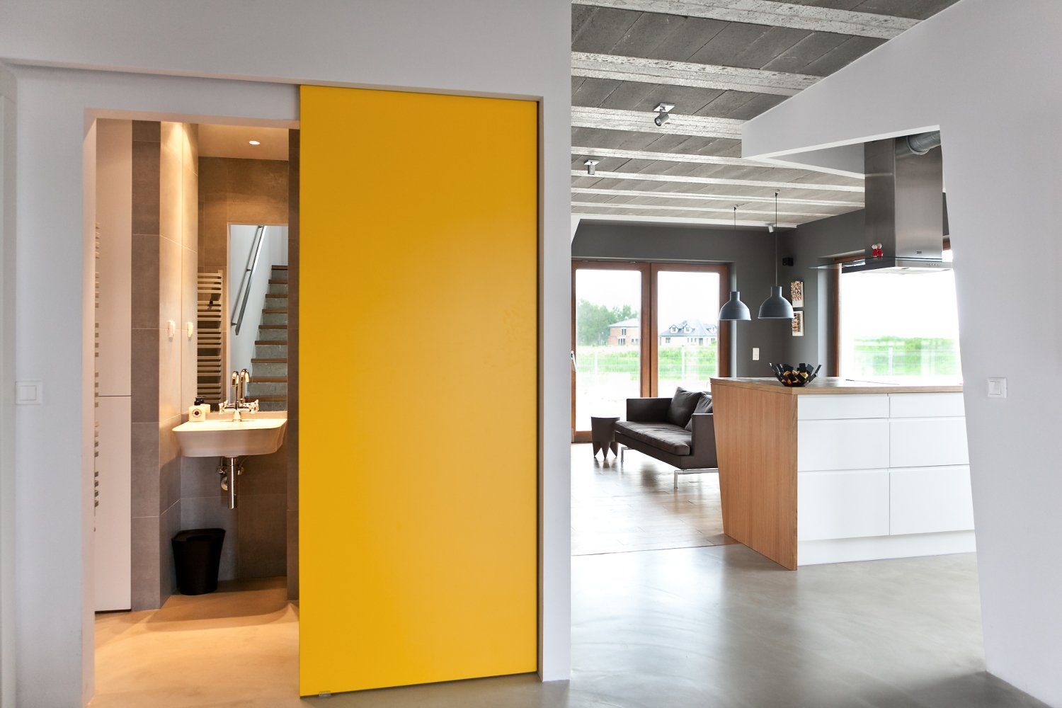 Kitchen, White Cabinet, and Wood Counter Canary yellow doors keep the house from feeling austere. The sliding function also saves space.  Photo 25 of 25 in 25 Bold Ways to Decorate with Yellow from How to Decorate With Yellow (Without the Smiley-Face Connotations)